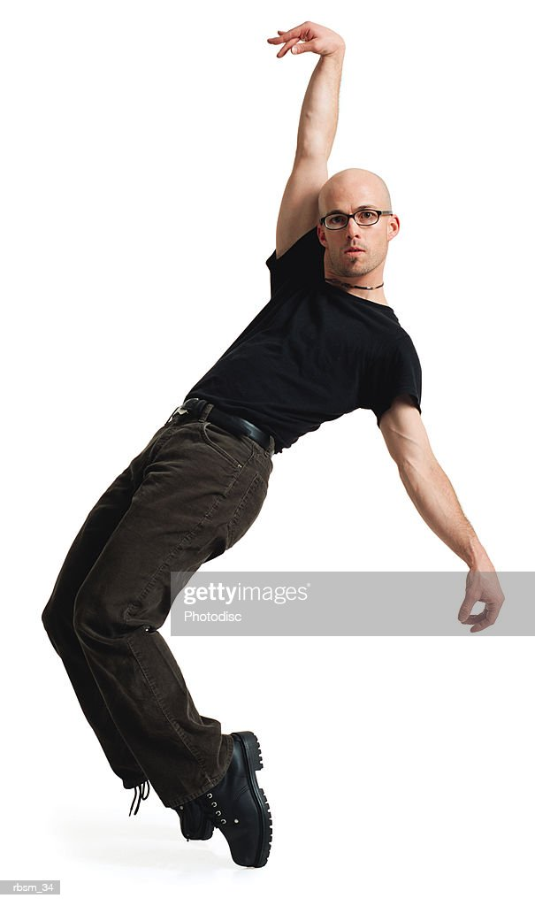 a young caucasian male modern dancer with a bald head in glasses black pants and t-shirt jumps up on heis toes arn raises one arm : Foto de stock