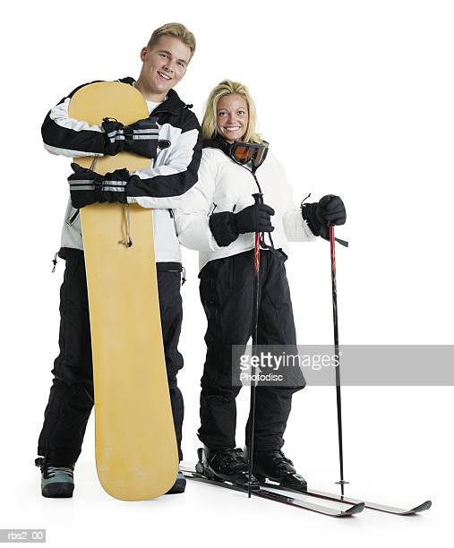 a young caucasian male snowboarder and a female caucasian skier stand with their gear and smile