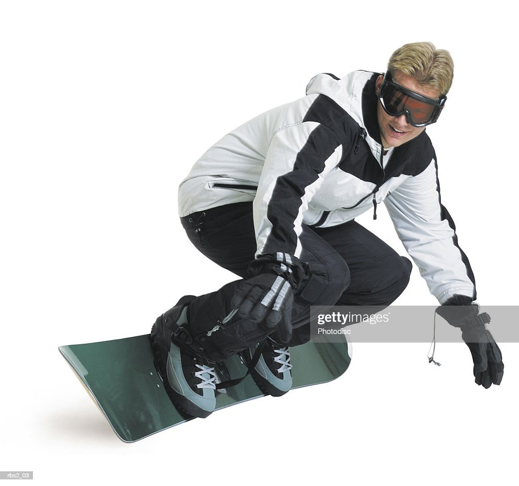 a young caucasian male snowboarder in a white and black jacket turns quickly while riding his board : Foto de stock