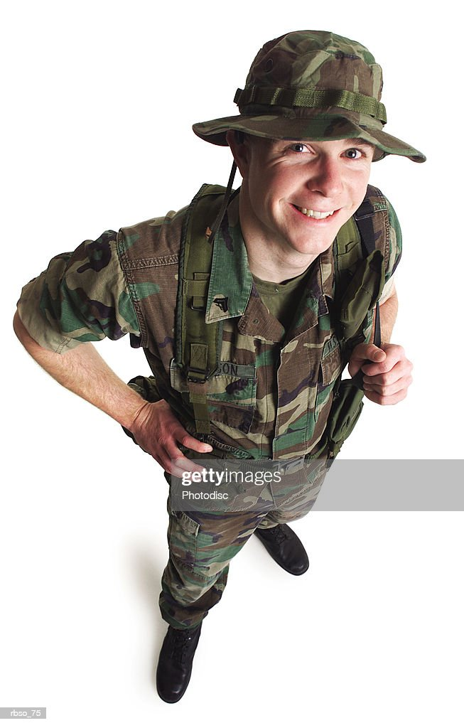 a young caucasian male soldier dressed in army fatigues smiles as he looks up at the camera : Foto de stock