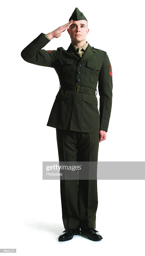 a young caucasian male soldier in his dress uniform stands at attention and salutes : Foto de stock