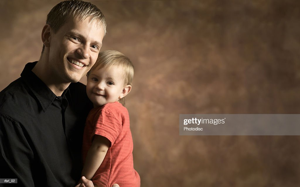 a young caucasian man holds up his cute baby daughter and smiles : Foto de stock