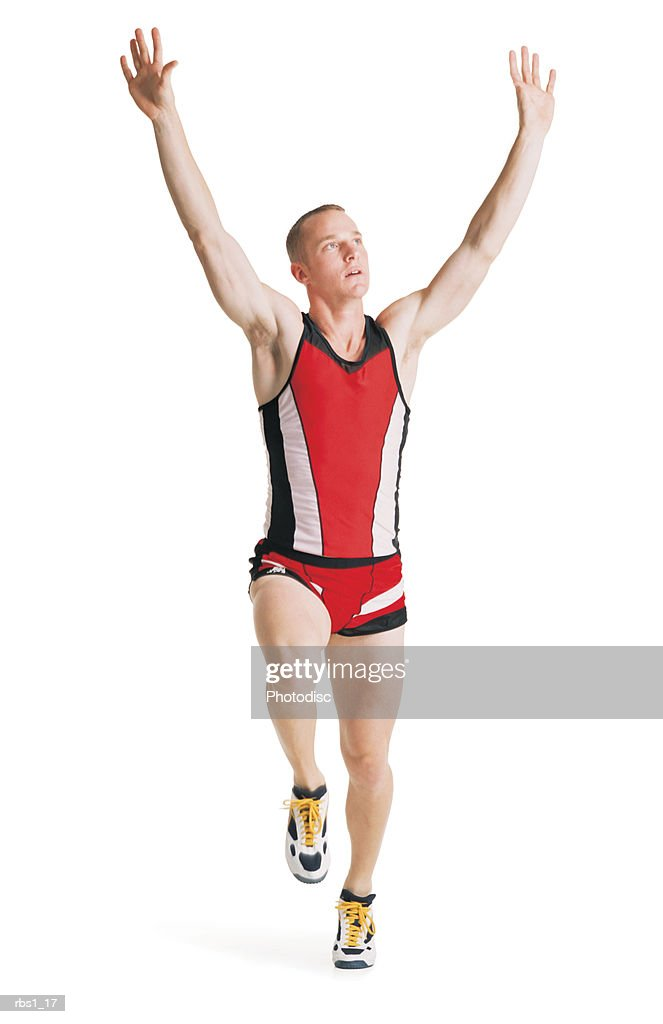 a young caucasian man in a red track uniform is running with arms raised overhead in a victory lap : Foto de stock
