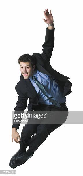 a young caucasian man in a suit playfully jumps up into the air - 背広 ストックフォトと画像