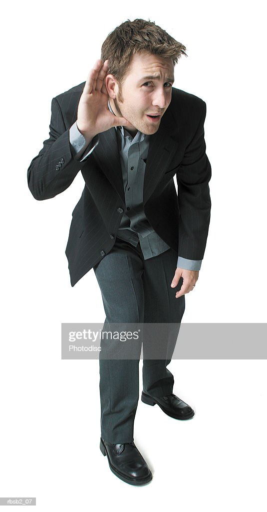 a young caucasian man in a suit puts a hand to his ear as if straining to listen : Foto de stock