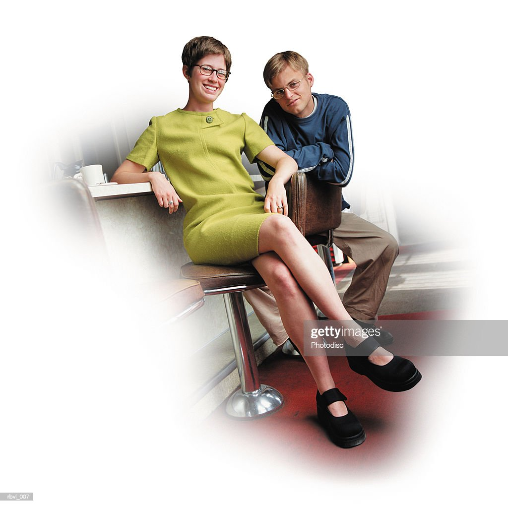 a young caucasian man in tan pants and a long sleeve blue shirt and a young caucasian woman in a short green dress are sitting on barstools in a cafe looking into the camera : Foto de stock