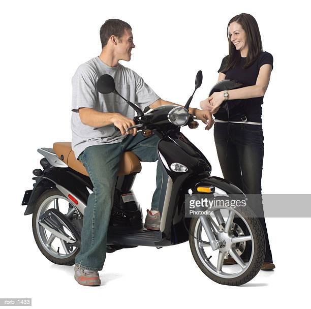 a young caucasian man on a motor scooter stops and chats with a young female
