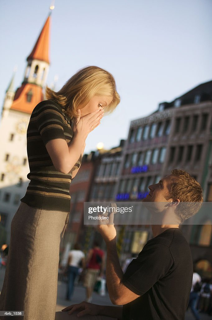 a young caucasian man propose marriage to his girlfriend while on vacation in europe : Stockfoto