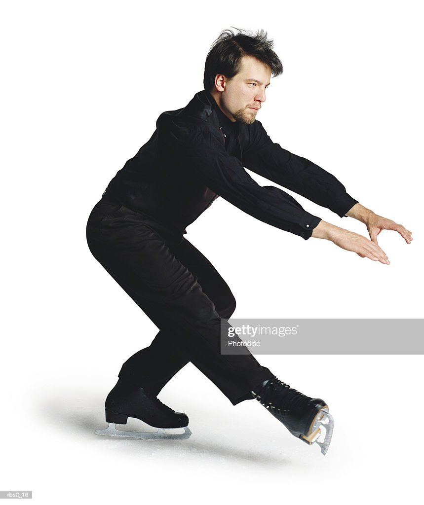 a young caucasian man wearing a black ice skating suit and ice skates is spinning around : Stockfoto