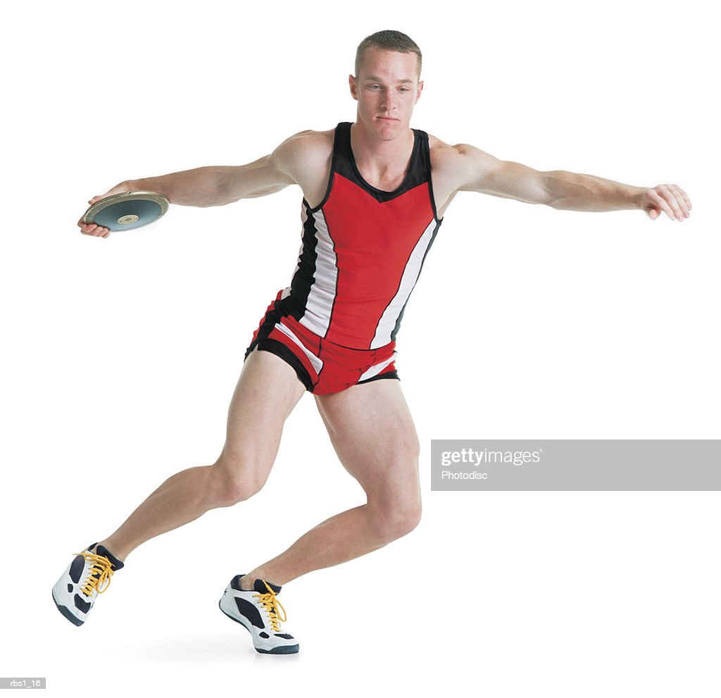a young caucasian man wearing a red track uniform is preparing to throw a discus as he spins on one foot : Foto de stock