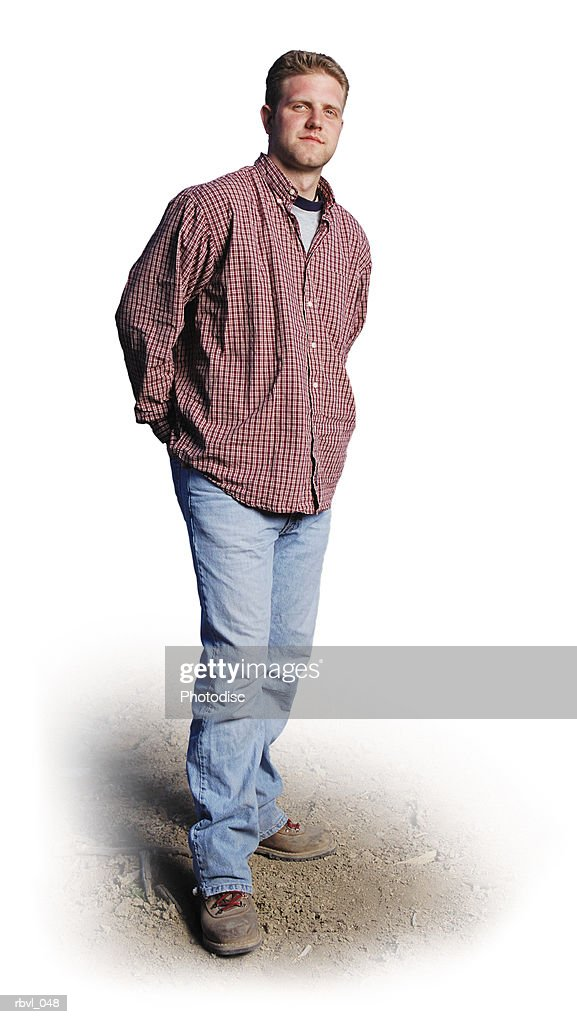 a young caucasian man with jeans and a red long sleeved shirt is standing outdoors looking into the camera : Foto de stock