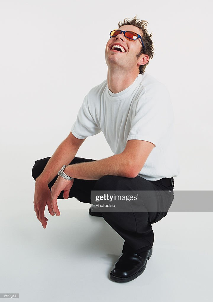 a young caucasian man with orange sunglasses and spiked hair is squatting down and wearing a white teeshirt and black slacks while throwing back his head and laughing : Foto de stock