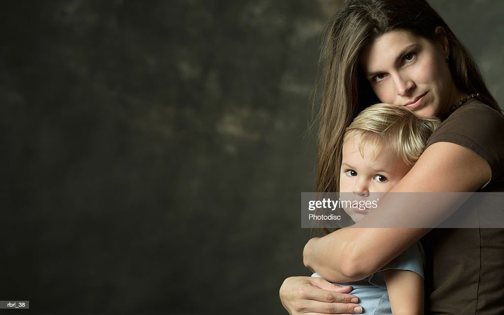 a young caucasian mother embraces her young blonde son on her lap : Stockfoto