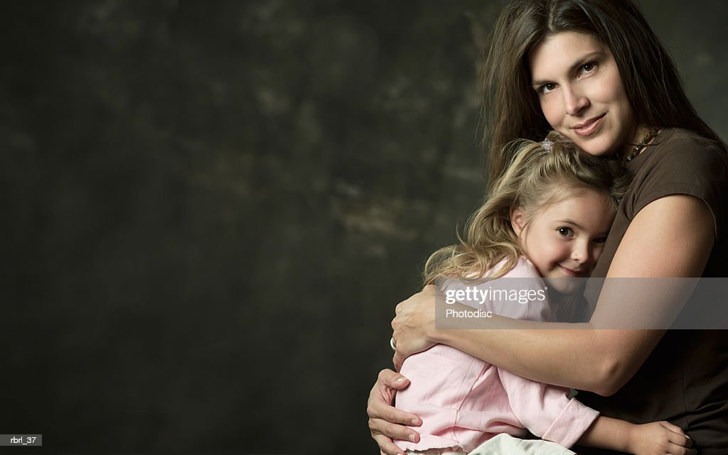 a young caucasian mother embraces her young daughter on her lap : Foto de stock