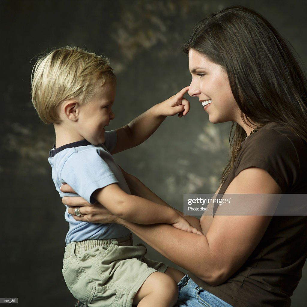 a young caucasian mother plays with her young blonde son on her lap : Foto de stock
