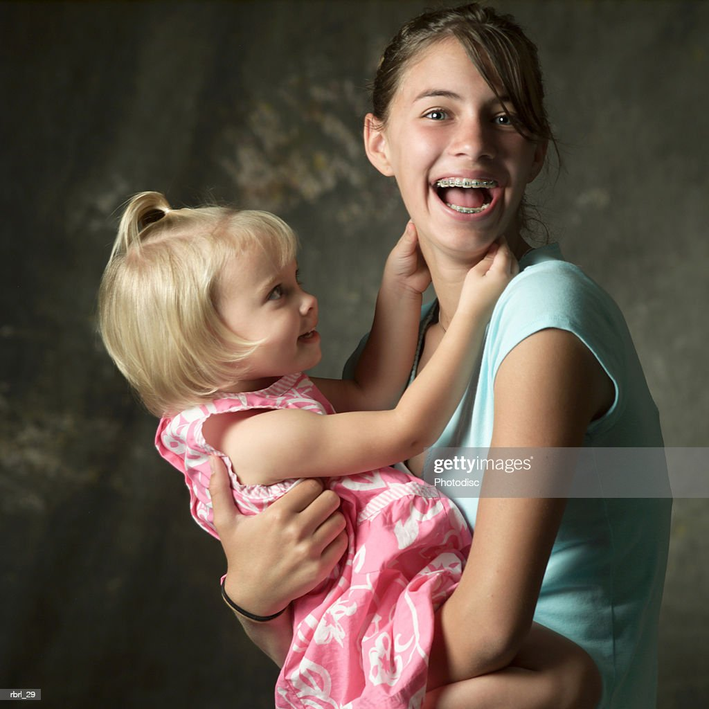 a young caucasian teenage girl laughs as she holds her little sister : Stockfoto