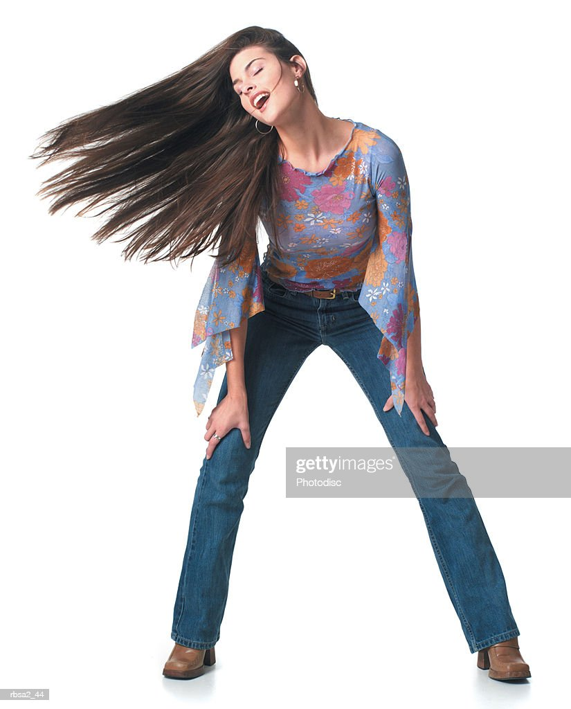 a young caucasian woman dressed in jeans and a multi colored shirt dances and playfully tosses her hair to the side : Foto de stock