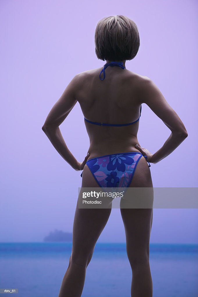 a young caucasian woman in a bikini puts her hands on her hips and looks out over the ocean : Foto de stock