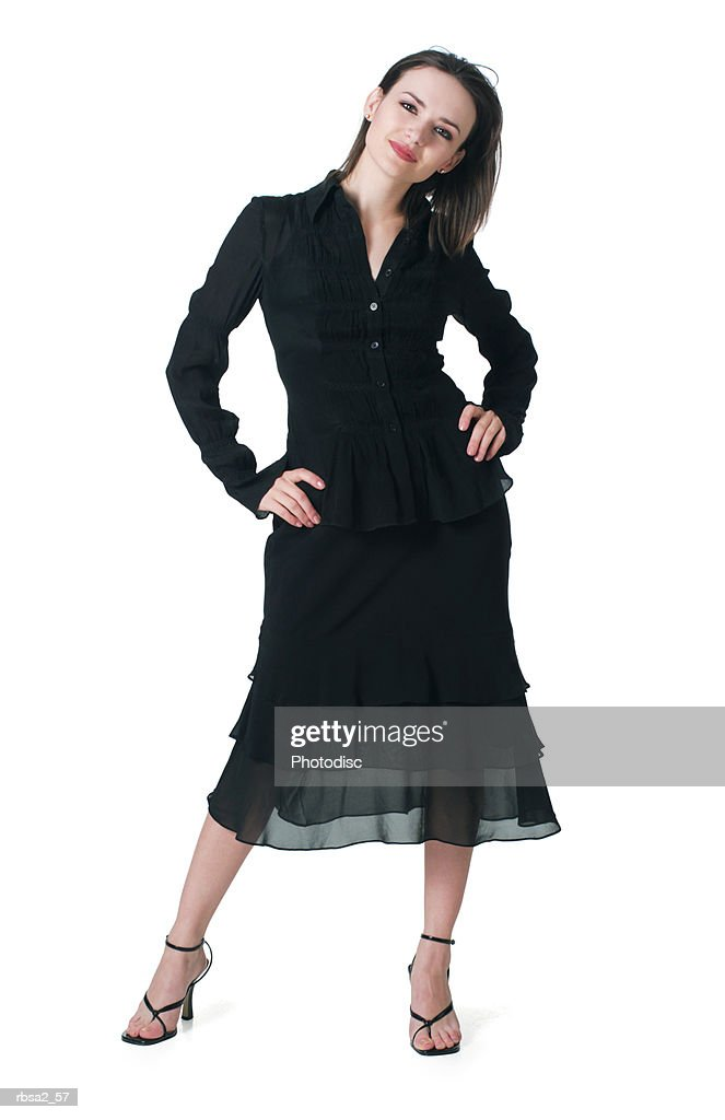 a young caucasian woman in a black dress leans her head to one side and smiles : Foto de stock