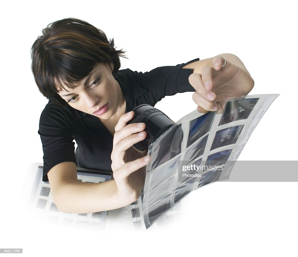 a young caucasian woman in a black dress looks at slides with a photo viewfinder : Stockfoto
