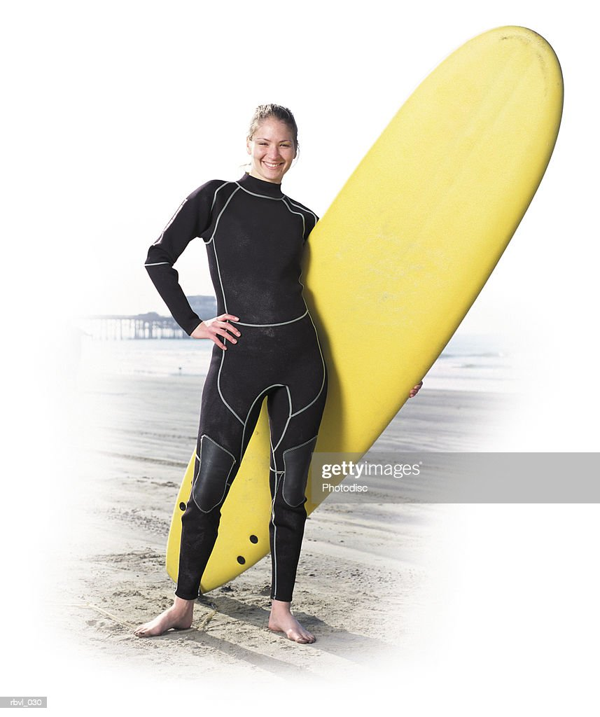 a young caucasian woman in a black wetsuit is standing on a beach holding her surfboard with the ocean in the background : Foto de stock