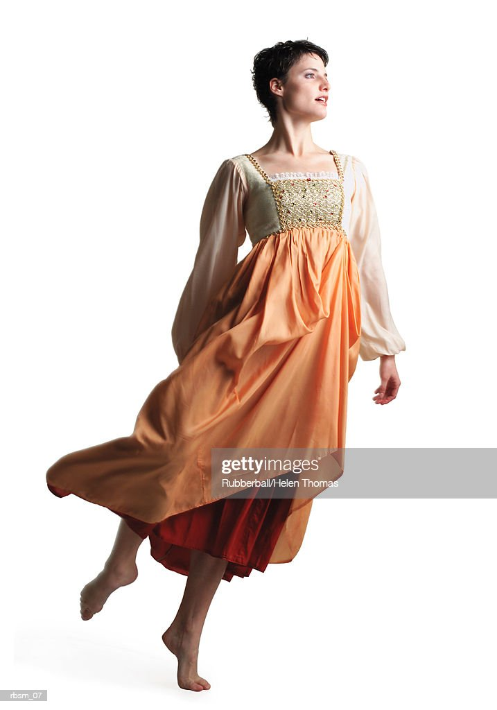 a young caucasian woman in a flowing period costume orange dress lifts herself up on her toe and spins : Foto de stock