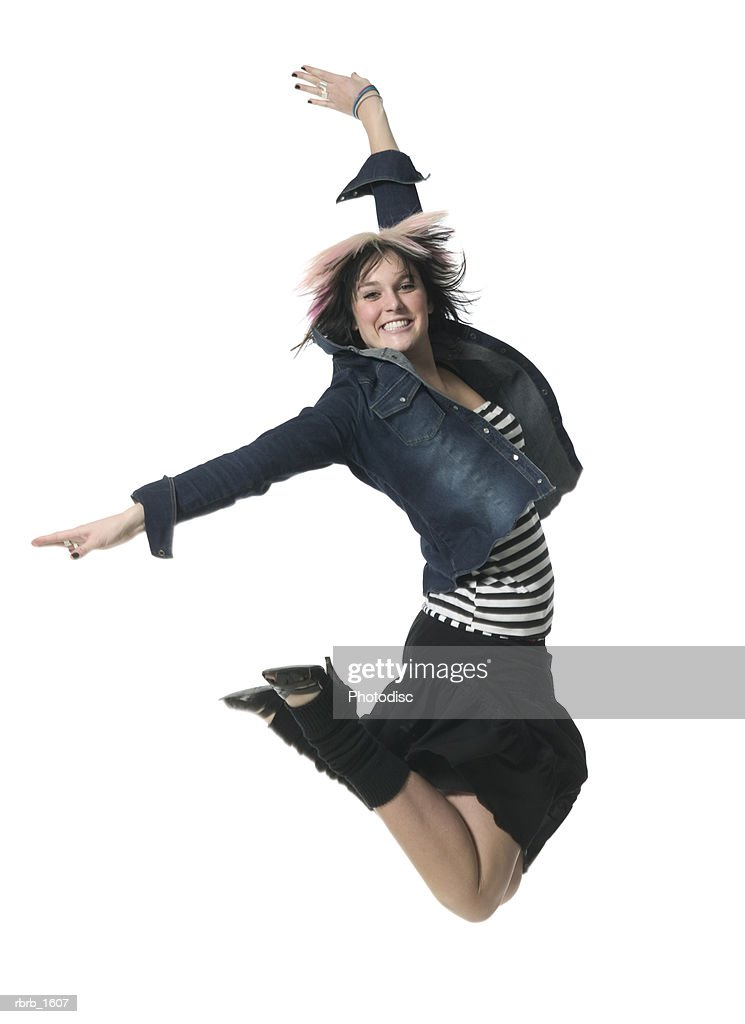 a young caucasian woman in a retro outfit jumps up wildly and smiles : Stockfoto