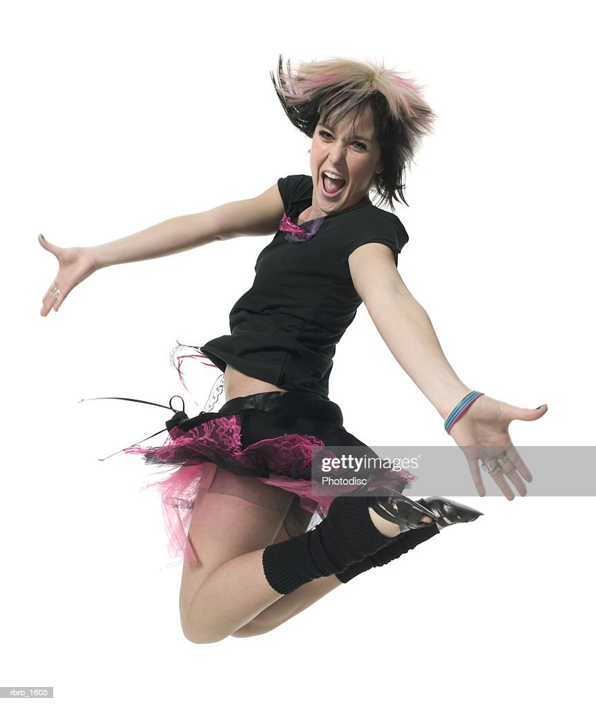 a young caucasian woman in a retro punk outfit jumps up into the air playfully : Stockfoto