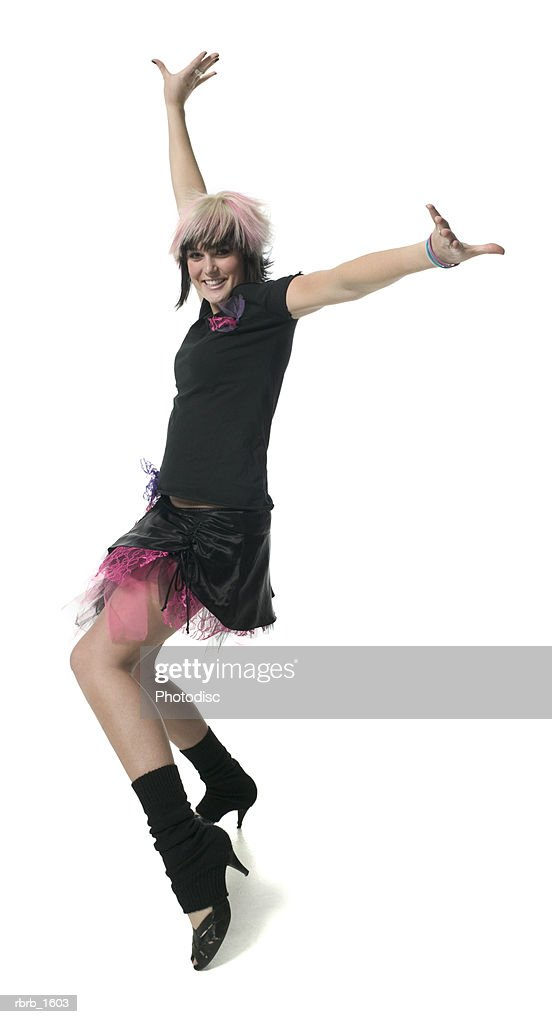 a young caucasian woman in a retro punk outfit strikes a fun dance pose : Stockfoto