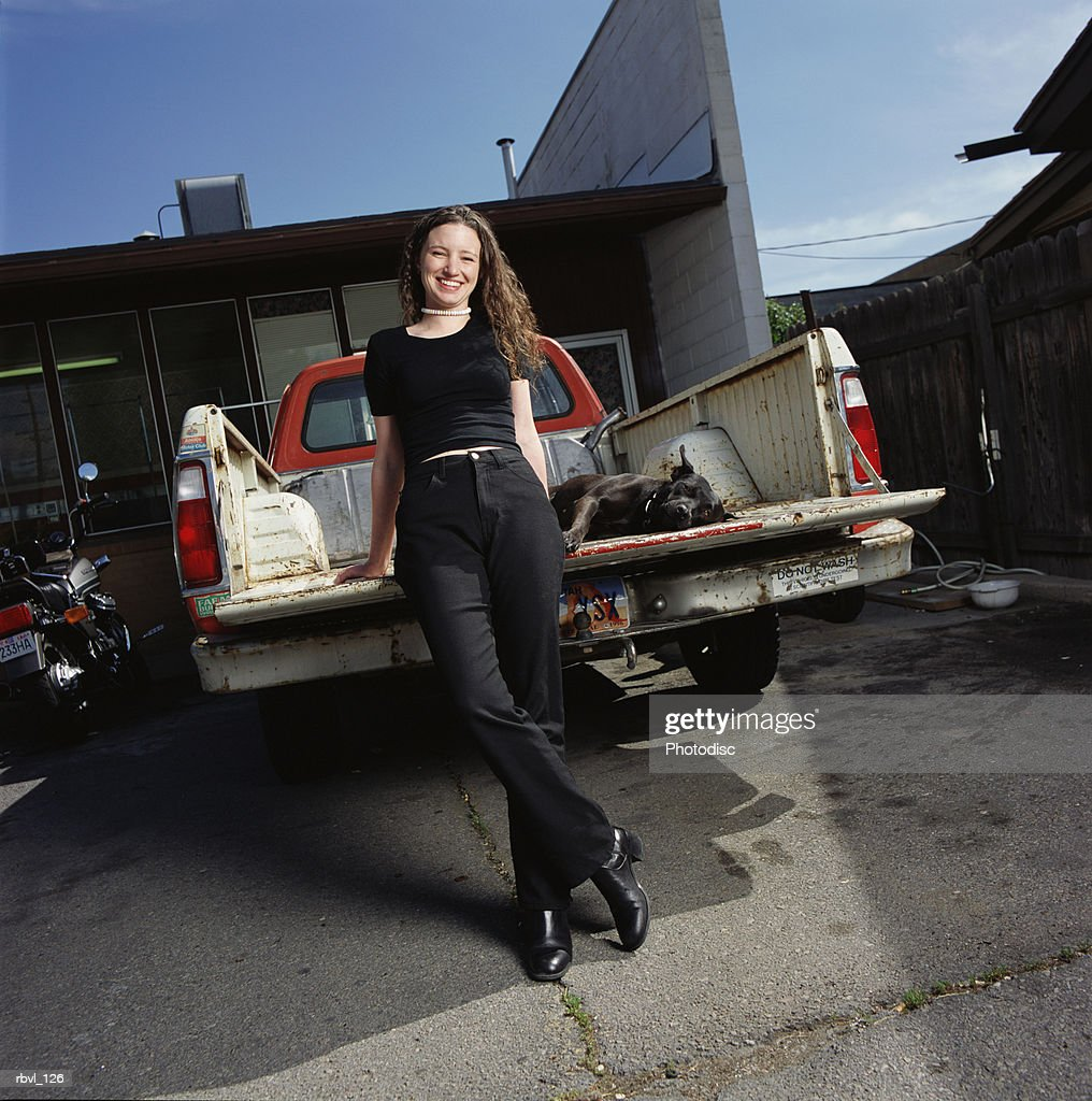 a young caucasian woman in black pants and shirt is leaning against the tailgate of a pickup truck with her black dog lying in the truck bed : Foto de stock