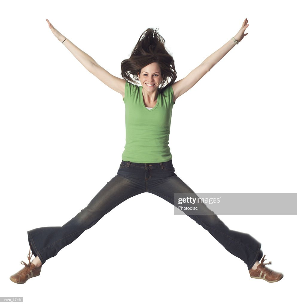 a young caucasian woman in jeans and a green shirt jumps up playfully through the air : Stockfoto