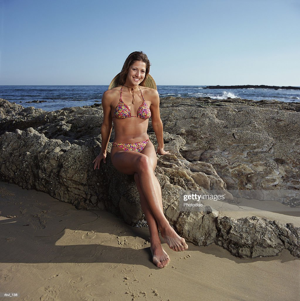 a young caucasian woman wearing a floral print bikini and a straw hat is sitting on a rocky coast with the ocean in the background : Foto de stock