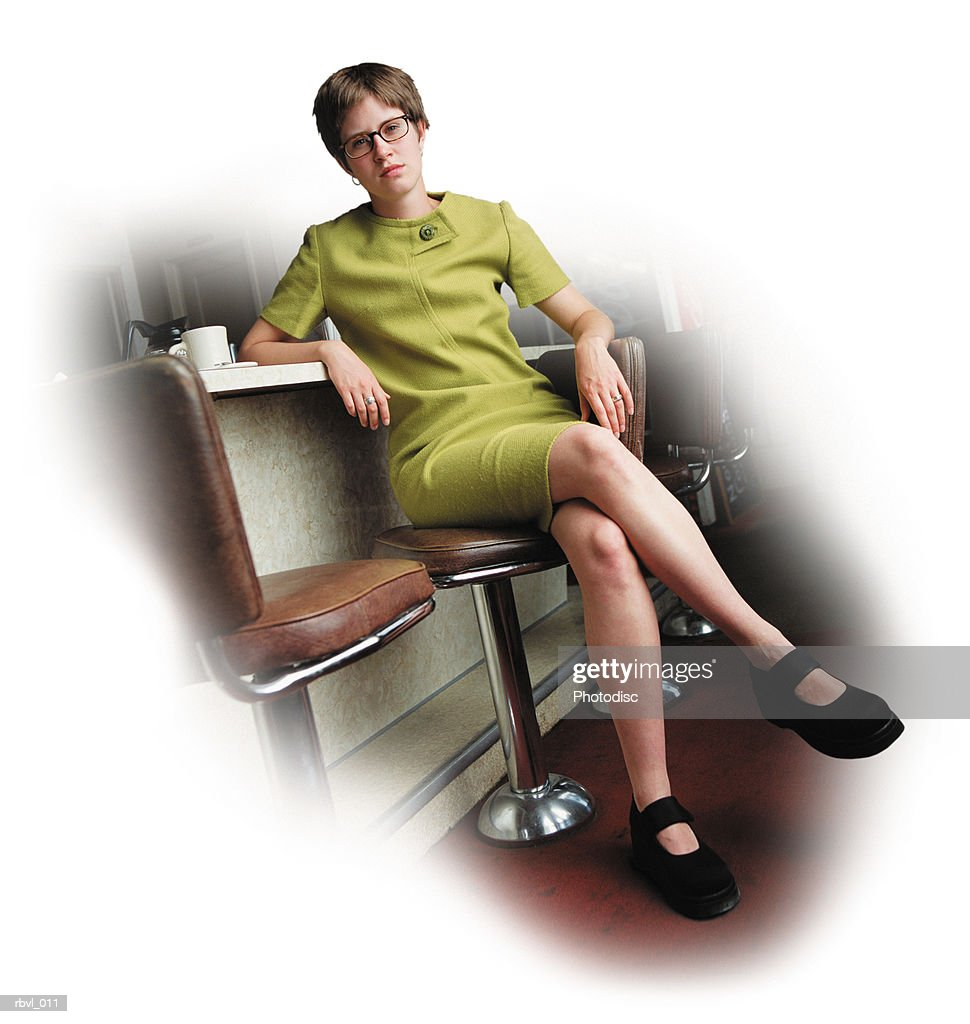 a young caucasian woman with a short trendy green dress and glasses is sitting at the bar of a diner looking seriously at the camera : Foto de stock