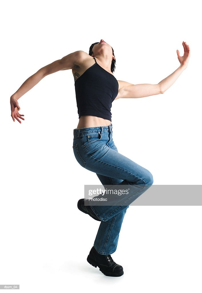 a young  caucsian woman in blue jeans and a black tank top dances wildly as she raises one leg and swings her arms up and out : Foto de stock