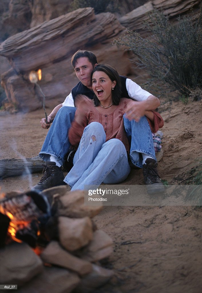 a young couple are sitting together by a campfire attemping to put out a marshmallow that has caught fire with the desert in the backgorund : Foto de stock