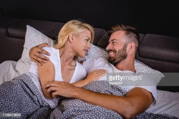 un jeune couple se réveillent au lit le matin - couple au lit photos et images de collection