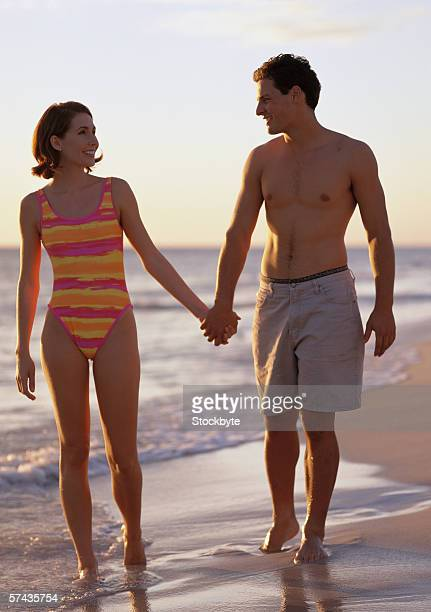 a young couple holding hands and walking on the beach