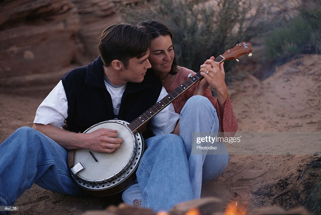 a young couple is sitting closely together beside a campfire where the man is showing the woman how to play the banjo with the desert  in the background : Foto de stock