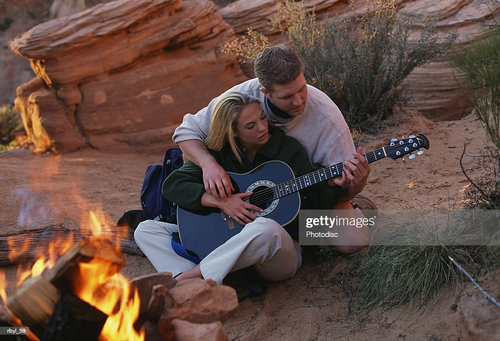 a young couple is sitting closely together beside a campfire where the man is showing the woman how to play the guitar with the desert  in the background : Foto de stock