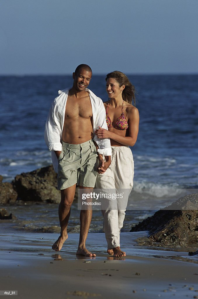 a young couple is walking along the shorline of a rocky beach holding hands and smiling lovingly at eachother : Stockfoto