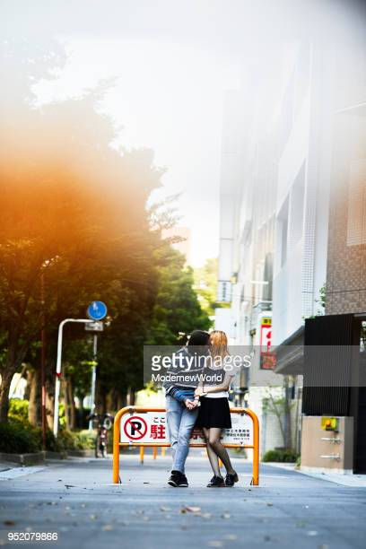 a young couple kissing on the street