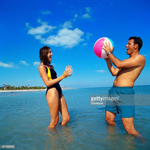 a young couple standing in the water and playing with a beach ball
