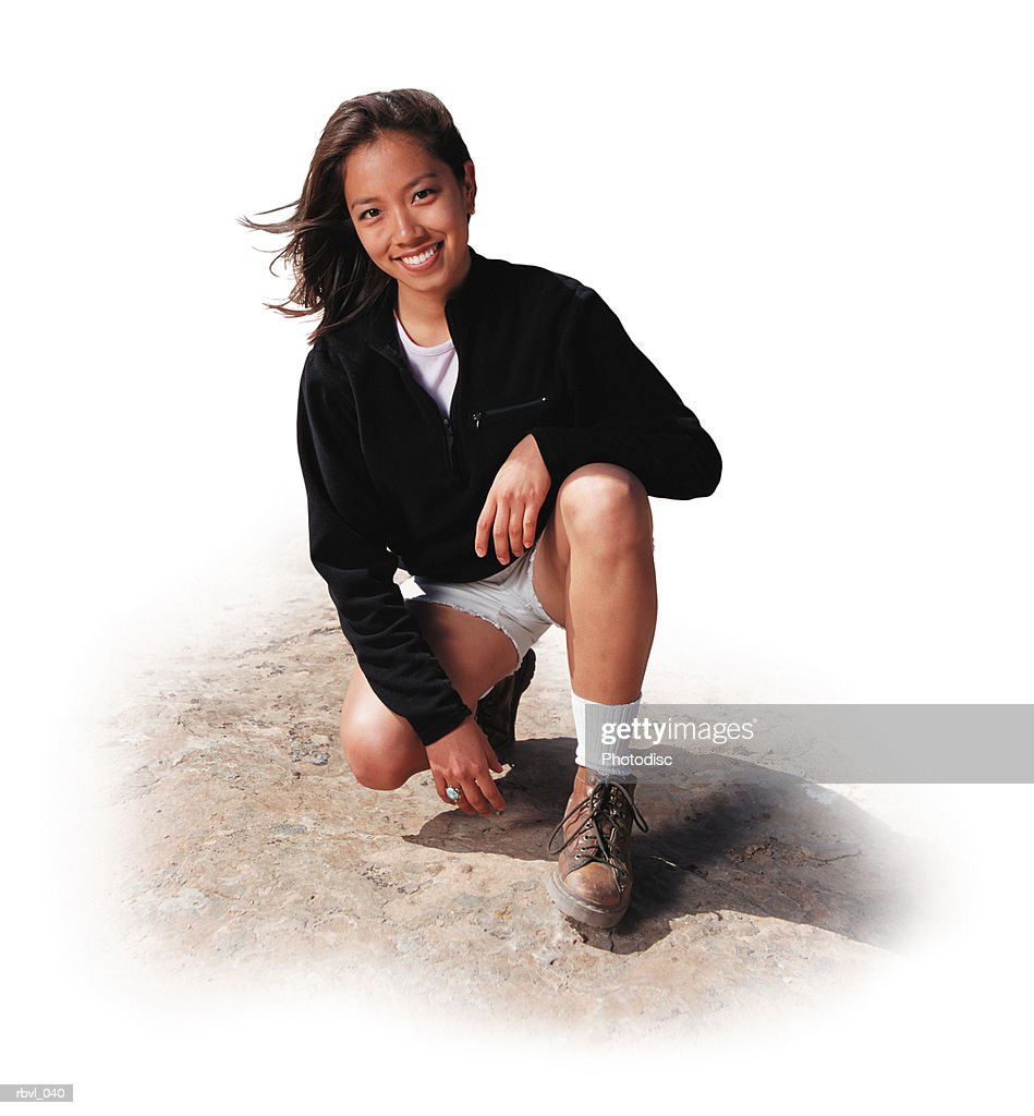 a young dark haired asian woman in white shorts and a black fleece jacket is crouching on a rock and smiling at the camera : Foto de stock