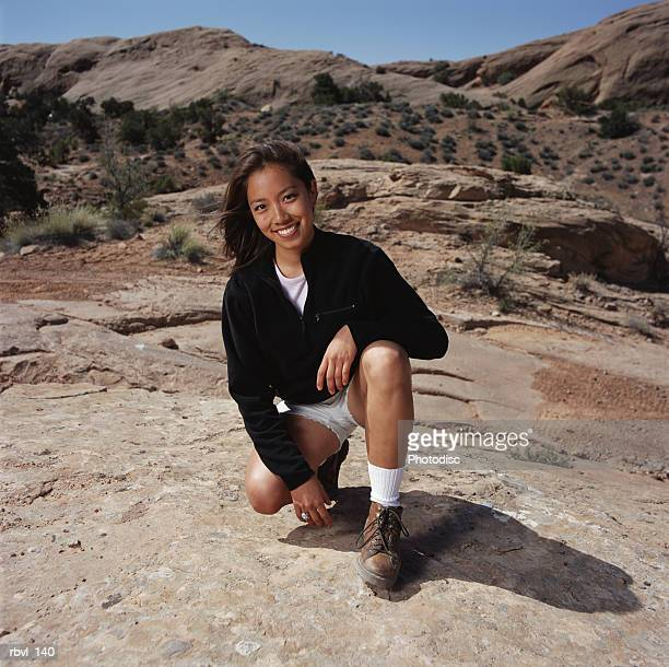 a young dark haired asian woman in white shorts and a black fleece jacket is crouching on a rock and smiling at the camera - fleecejas stockfoto's en -beelden