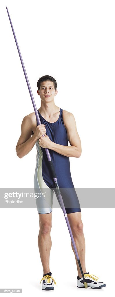 a young dark haired ethnic male track and field participant in a blue jumpsuit holds a javelin up against his shoulder and smiles : Stockfoto