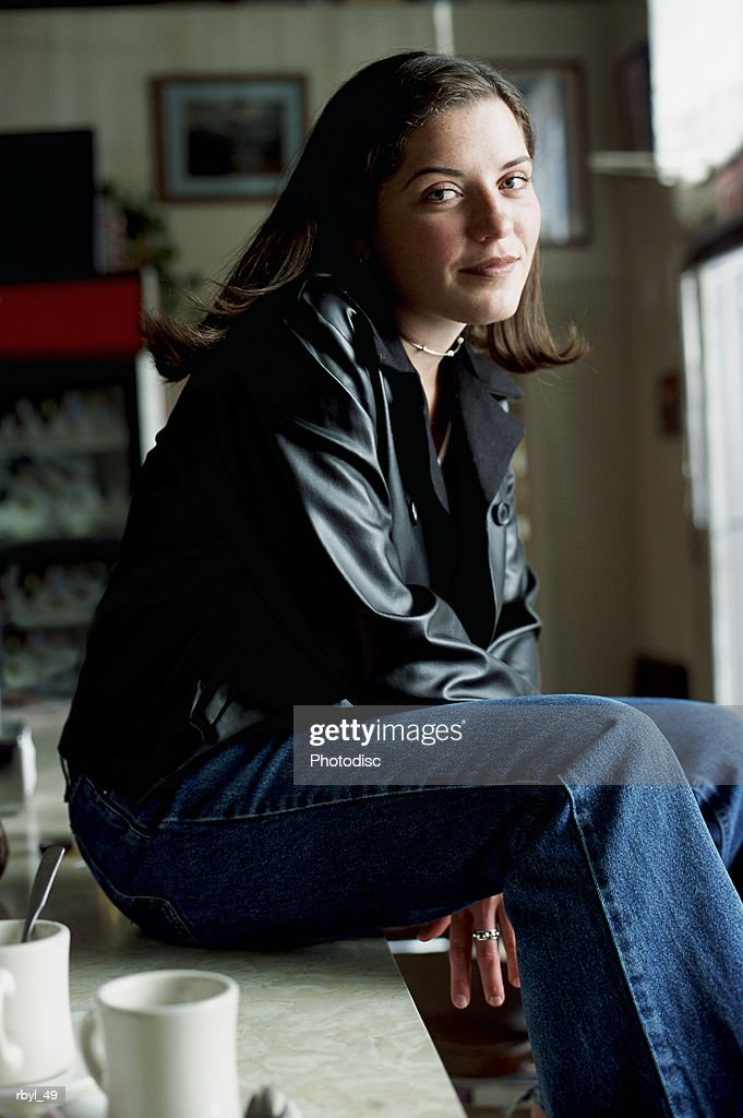 a young dark haried woman is sitting on the counter of a cafe or diner or cafe looking into the camera and smiling : Foto de stock