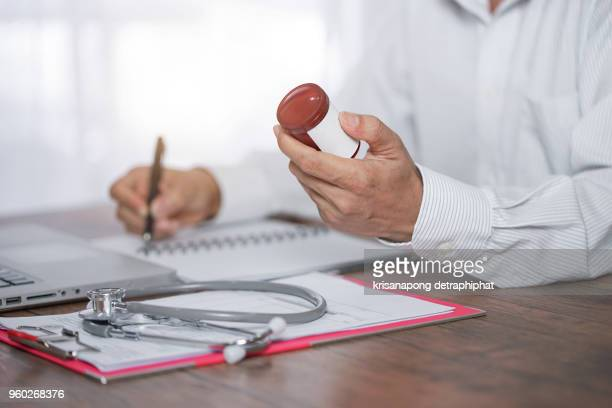 a young doctor prescribes medication. prescription pills are prescribed by the doctor. - fee stock pictures, royalty-free photos & images