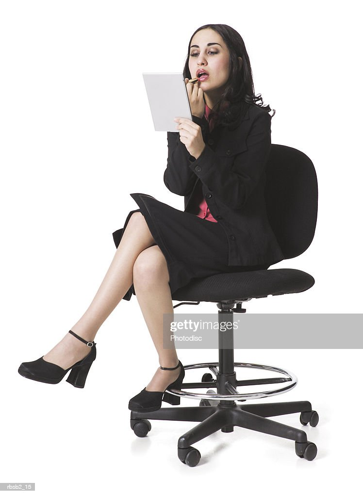 a young ethnic business woman sits on a chair and fixes her make up : Foto de stock
