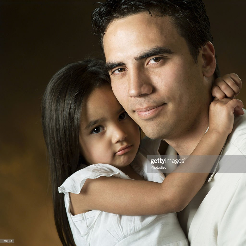 a young ethnic father loving recieves a hug from his little daughter : Foto de stock