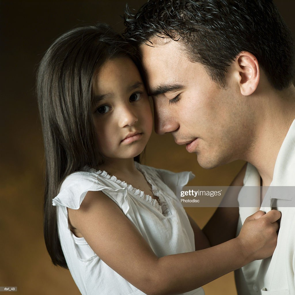 a young ethnic father loving rest his head against the head of his little daughter : Foto de stock